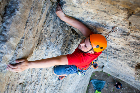 strong: Climber in a helmet climbs to the top of the mountain. Sport activities in nature.