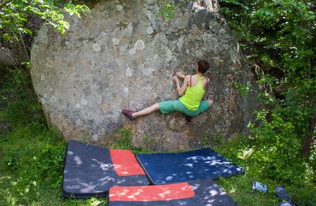 Kletterer bouldert in der Natur. Mädchen klettert auf einen großen Stein Frau macht Sport im Freien. Athlet ist in der Tätigkeit im Freien beschäftigt.