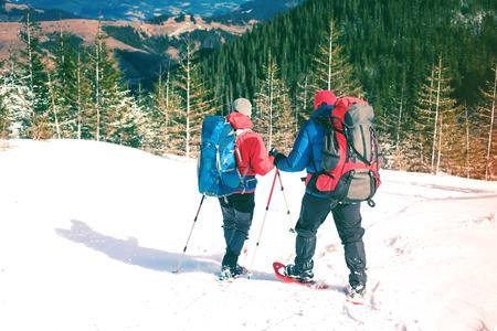 Zwei Kletterer sind in den Bergen im Winter gegen schneebedeckte Tannenbäume und klettern zwei Männer mit Rucksäcken. Standard-Bild - 79008871