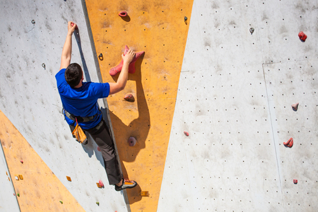 rockclimbing: A young man climbs on the climbing wall.