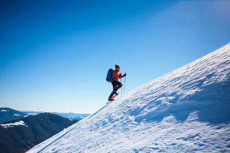 Climber with backpack, trekking poles, snowshoes rises to the top of the mountain in the snow on a background of beautiful blue sky.