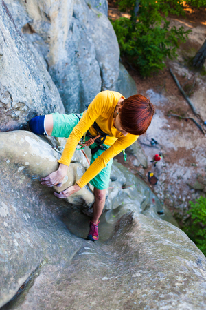 Sports girl climbs on the rock. Climbing in nature, active rest on a day off. Stock Photo
