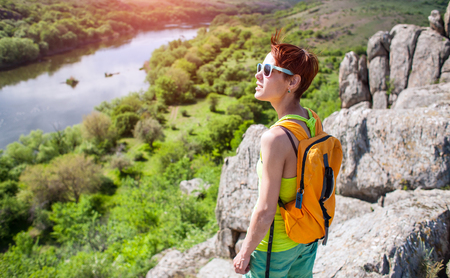 Girl with a backpack walks in picturesque places. A woman resting in nature. Active person walking in rocky hill. A young woman in the mountains is on the background of the river.