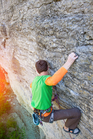 A strong climber in the green shirt climbs on the rock. extreme sports in nature.