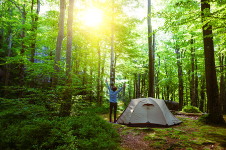 The girl is standing near the tent. Morning yoga in the forest after awakening. Stock Photo
