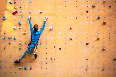 A young woman with short hair climbs on the climbing wall. Stock Photo