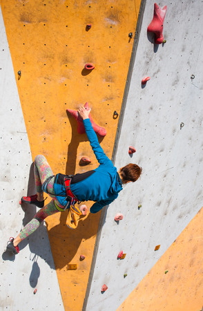 bouldering: A young woman with short hair climbs on the climbing wall. Stock Photo