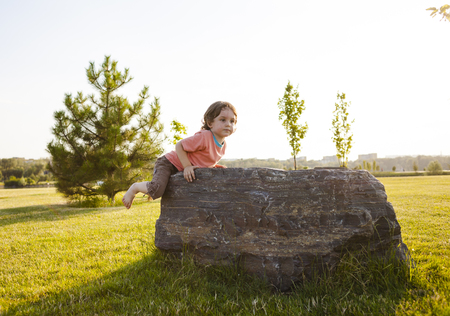 The little boy climbed a stone. Walk in the park and climbing on the rocks. Bouldering in nature.
