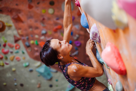 clambering: Climbing on a climbing wall. The climber is climbing the route in the hall. Bouldering in the city. Stock Photo