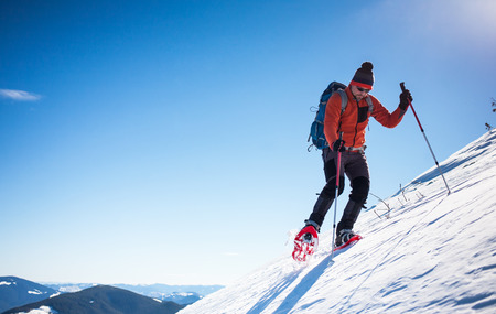 snowshoes: Climber with backpack, trekking poles, snowshoes rises to the top of the mountain in the snow on a background of beautiful blue sky.