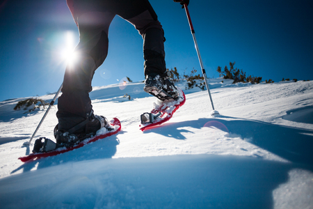Man in snowshoes with trekking poles is the snow in the mountains.