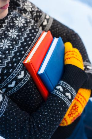 La niña en el suéter y las manoplas de punto tiene dos libros contra la nieve del invierno. Foto de archivo - 84133981