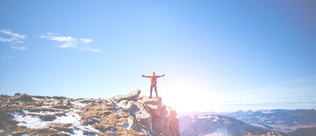 The mountaineer climbed the mountain, stands on top and is reaping the success, a man stands on a cliff, arms outstretched.
