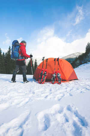 The mountaineer stands near the camp with a tent and snowshoes. Active rest and mountain climbing in winter in the mountains. Stock Photo