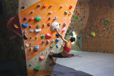 Climbing on a climbing wall. The climber is climbing the route in the hall. Bouldering in the city. Stock Photo