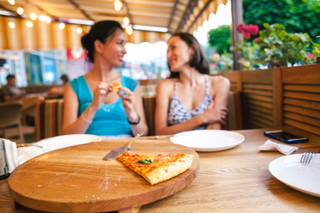 Two girls are eating pizza. Girlfriends have fun at the cafe. Women share the last piece of pizza. Brunettes have lunch in the restaurant.