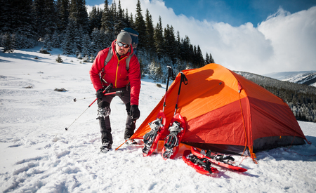 The climber puts a tent near the camp with a tent and snowshoes. Active rest and mountain climbing in winter in the mountains.