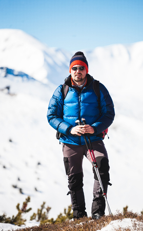 cold: Man with trekking poles goes up in the mountains in winter, the climber with a backpack walking on snow on a Sunny day on the background of blue sky. Stock Photo