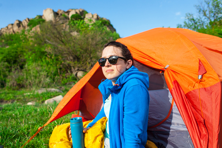 Camping in the forest. The girl is drinking coffee from a thermo mug near the tent against the background of the mountains. A woman sits near a tent in a sleeping bag and drinks tea from a thermos.