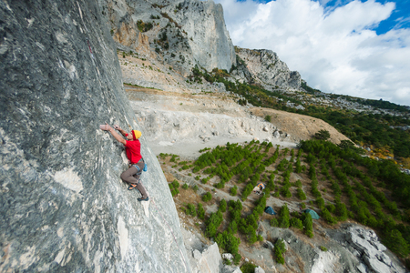 A rock climber on a rock. A man climbs the rock on the background of a beautiful mountain landscape and sky with clouds. Active lifestyle. Sports in nature. Overcoming a difficult climbing route. Stock Photo