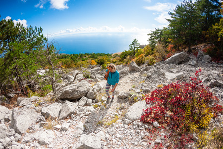 A girl walks along the mountain path on the background of the sea coast. A woman walks along a stony path on a background of mountain scenery and sky with cloud. A blonde is traveling with a backpack. Stock Photo