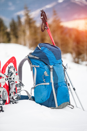 Blue backpack, red snow shoes and trekking poles stand in the snow on the background of spruce forest and mountain in winter.