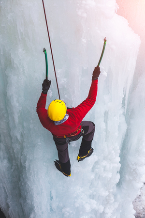 A young climber climbs on ice climbing and winter sport activities in cold weather.  Banco de Imagens