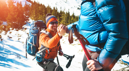 Climber helping teammate climb, the man with the backpack reached out a helping hand to his friend.
