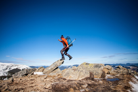 Escalador con una mochila en la parte superior en un día soleado, un hombre con bastones de trekking subió a la montaña, las personas que viajan a través de la hermosa naturaleza. Foto de archivo - 89767510