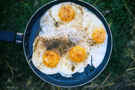 Scrambled eggs with black pepper are fried in a frying pan. Cooking in the open air. Picnic in nature. Camping in the forest. Stock Photo