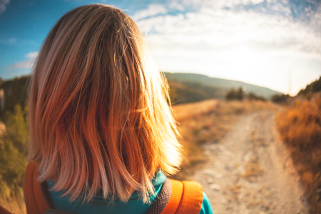 A girl with a backpack walks along the mountain path. A woman is walking through the forest at sunset. A blonde is traveling with a backpack. Hair beautifully fluttering in the wind. Standard-Bild