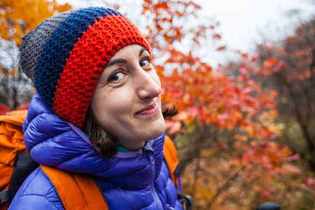 A girl with a backpack walks along a forest trail. Skyrunning in the fall. Active recreation in nature. A woman is walking on a dirt road. Portrait of a smiling girl in a knitted cap.