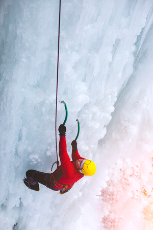 A young climber climbs on ice climbing and winter sport activities in cold weather.  Stock Photo