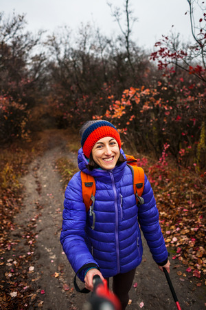 A woman with a backpack does selfie. A girl with trekking sticks walks along a forest trail. Trekking in autumn. Skyrunning in the fall. A woman is walking on a dirt road. Girl in a knitted cap.