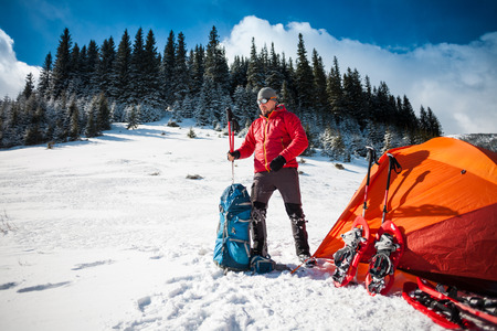 The climber gathers equipment near the tent before climbing the mountains. man with a backpack near the camp. Snowshoes and a tent in the mountains in winter. Stock Photo