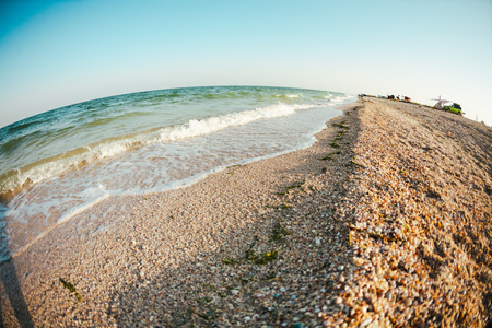 Sea coast at sunset. The shore of the ocean. Waves break on the sandy shore. Stock Photo