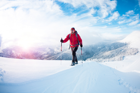 A man in snowshoes in the mountains in the winter. A climber with trekking sticks walks through the snow. Winter ascent. Beautiful sky with clouds.