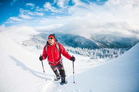 スノーシューとトレッキングを着た男が山に突っ込む。冬の旅雲と美しい空に対する登山。アクティブなライフスタイル。雪の中を登る