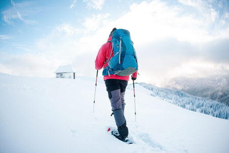A man in snowshoes in the mountains in the winter. A climber with trekking sticks walks through the snow. Winter ascent. The house is covered with snow. Beautiful sky with clouds.