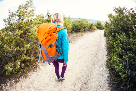 A girl with a backpack walks along the mountain path against a beautiful blue sky with clouds. A woman walks along a stony path. A blonde is traveling with a backpack. Stock Photo