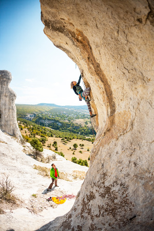 Two climbers are trained on a large boulder. Extreme sport. Active recreation in nature. A woman overcomes a difficult climbing route on the background of beautiful mountain valley.