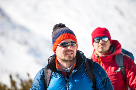 Climbers walk through the snow in the mountains. Walking tour with backpacks. Winter holidays in the mountains.