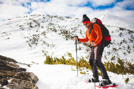 Mountaineer in snowshoes carry a backpack. Journey in the mountains in winter. Extreme vacation in nature.