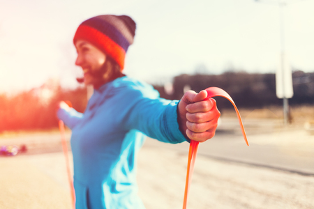 girl doing exercises in the street with a rubber band. exercise fitness on the street. a healthy lifestyle and a beautiful body.