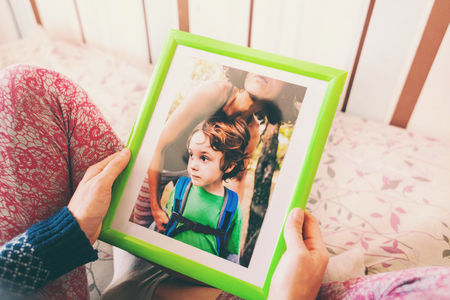 Mom holds a photo frame with a photograph of her son. A small child and memories. Stock Photo