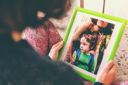 A woman looks at a photo of a boy. Mom holds a photo frame with a photograph of her son. A small child and memories. Stock Photo