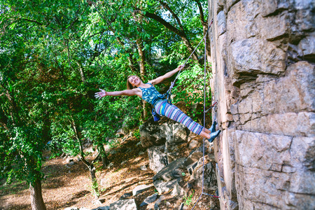 outdoor activities in the forest. the climber climbs the rock. a healthy lifestyle and an extreme sport. Stock Photo