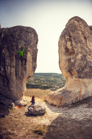 Two climbers are trained on a large boulder. Extreme sport. Active recreation in nature. A man overcomes a difficult climbing route on the background of beautiful mountain valley.