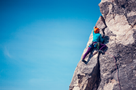 The girl climbs the rock against the sky. The climber in helmet trains on a natural relief. Extreme sport. Active recreation in nature. A woman overcomes a difficult climbing route.