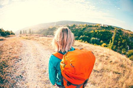 A girl with a backpack walks along the mountain path. A woman is walking along a stony road. Blonde with an orange backpack. Stock Photo
